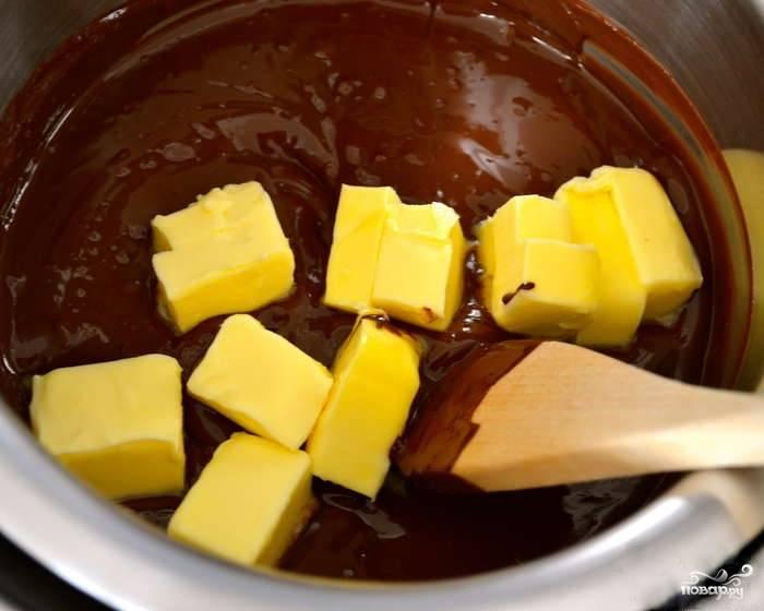 2.Шоколад растопите на водяной бане, добавьте к нему 100 г. сливочного масла, хорошо перемешайте. Оставьте немного остыть.