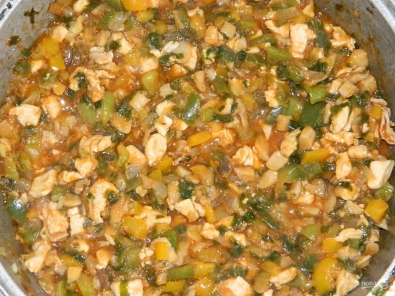 Следом на плиту отправьте курицу, томатную пасту, соль, сливочное масло и сахар. Тушите начинку для конвертов ещё 20 минут.