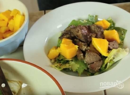И формируем салат. Раскладываем по тарелкам зелень, печень и добавляем манго. Сверху еще немного поливаем соусом и посыпаем перцем.