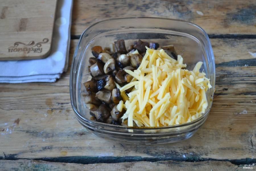 А для начинки очистите шампиньоны и нарежьте некрупным кубиком. Обжарьте их на сковороде до готовности. Не забудьте слегка присолить. Затем смешайте обжаренные грибы с натертым сыром, хорошенько перемешайте.