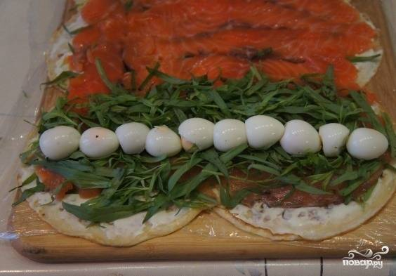 С той стороны блинного полотна, где рыба выложена с самого края, выкладываем полосу зелени, а посередине выкладываем яйца.