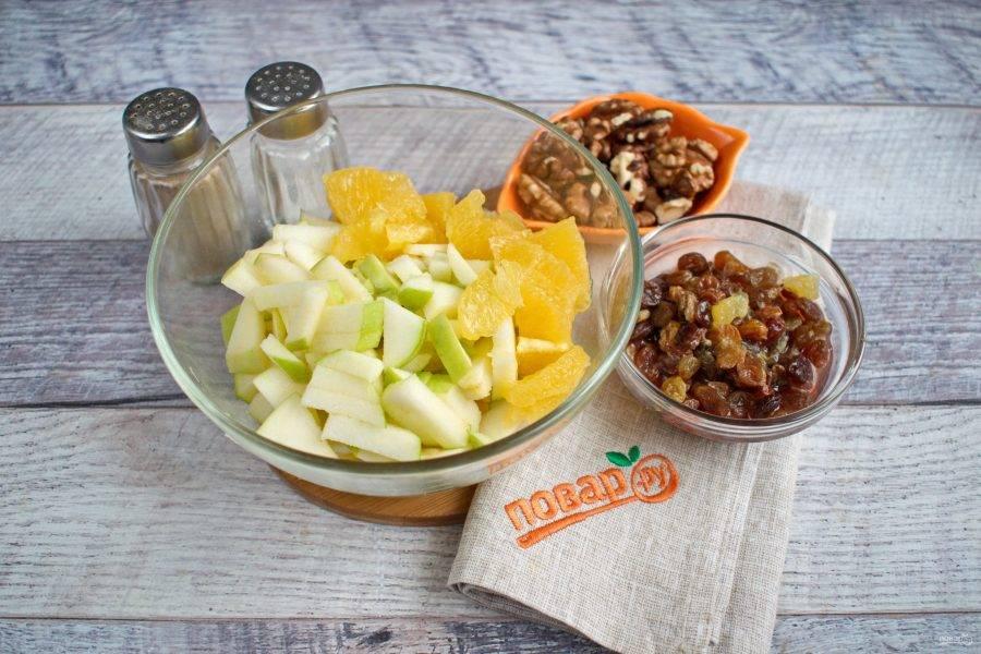 Апельсин очистите от кожуры  и белых перегородок. В миске соедините масло, уксус, залейте смесью изюм на 5 минут. Яблоки нарежьте кусочками, которые вам будет удобно накалывать на вилку. Апельсиновые ломтики - пополам, ореховые ядра - на четвертинки.