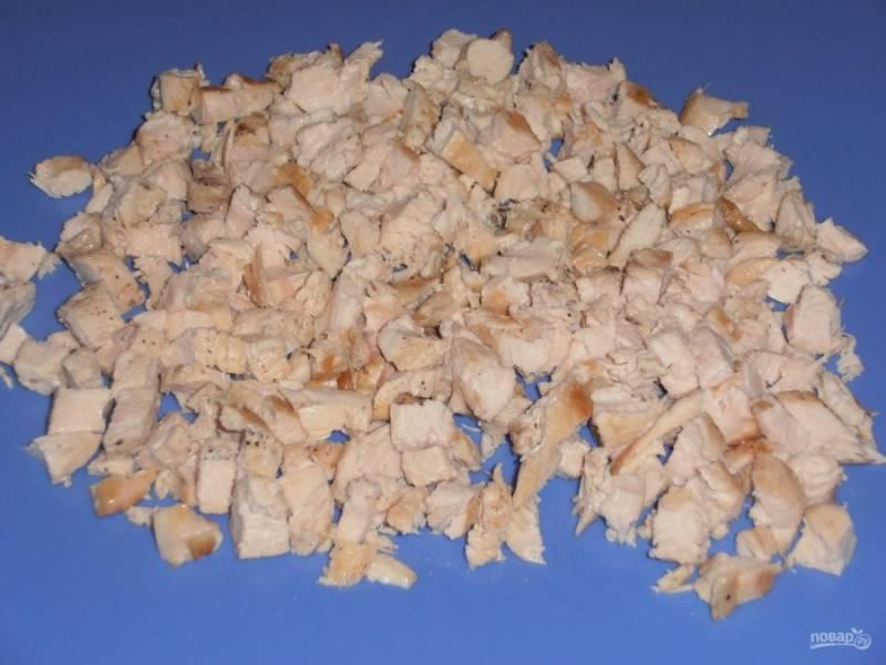 Куриную грудку промойте и обсушите. Затем отварите до готовности. Остудите и нарежьте небольшими кубиками.