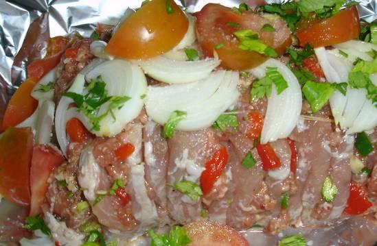 Форму для выпечки застелите фольгой, поместите в центр мясо, а сверху выложите тонко порезанный лук и помидоры. Полейте маслом, заверните в фольгу и выпекайте в духовке 45 минут.