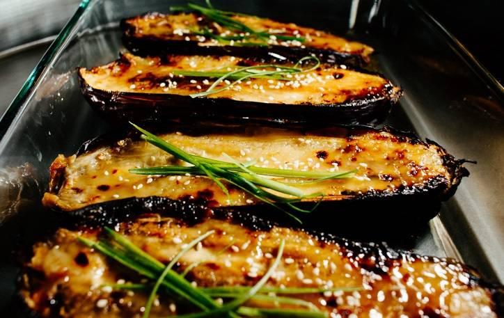 4. Полить карамельным соусом баклажаны (оставив немного для подачи) и присыпать кунжутом. Отправить в духовку еще на пару минут. После выложить сверху перья зеленого лука.