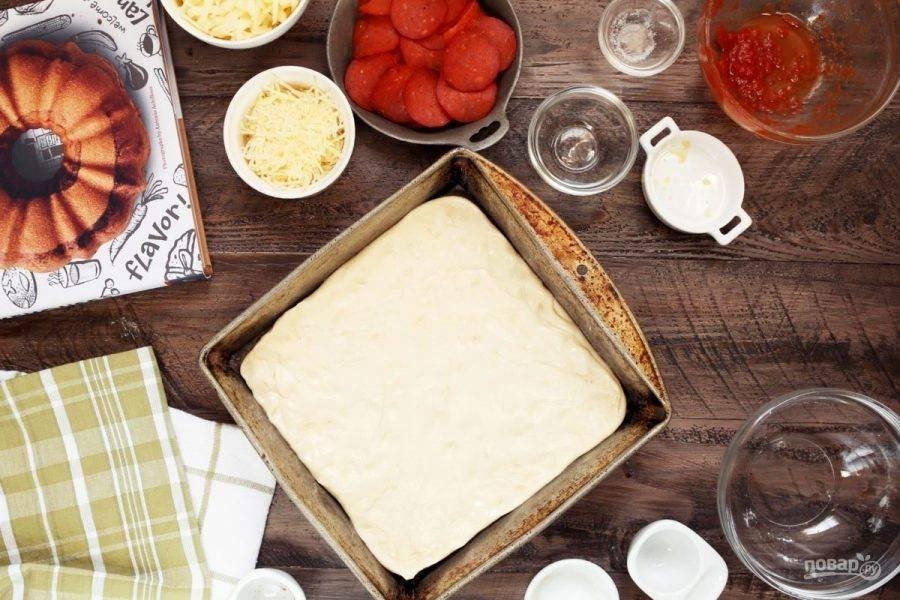 4.Форму для пиццы смажьте растительным маслом, раскатайте тесто и выложите его в форму, разровняйте руками.
