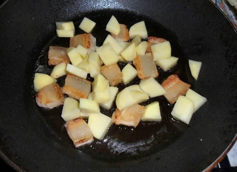 Как только сало станет золотистого цвета и на сковороде будет достаточное количество жира, выкладываем на нее очищенный и нарезанный кубиками картофель, жарим его пару минут.