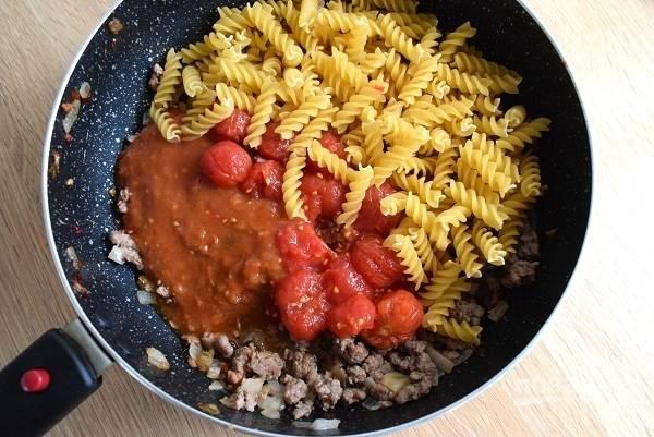 Снимите с помидоров кожицу, порежьте мякоть и отправьте в сковороду. Добавьте остальные ингредиенты, перемешайте. Долейте воды столько, чтобы она едва покрыла фарш, и накройте крышкой.