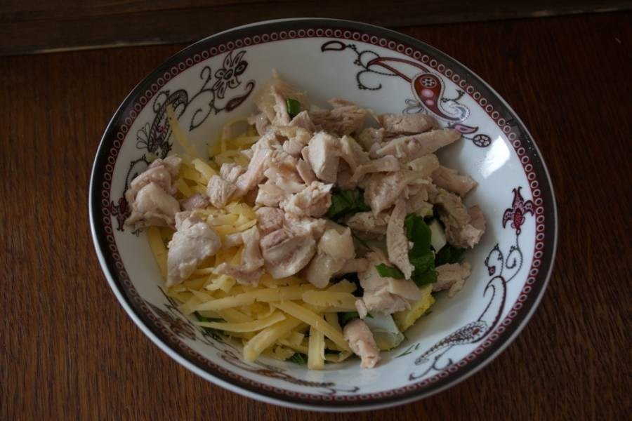 Соедините в одной емкости зелень, огурцы, сыр, отварную куриное мясо, яйцо. Заправьте салат майонезом.