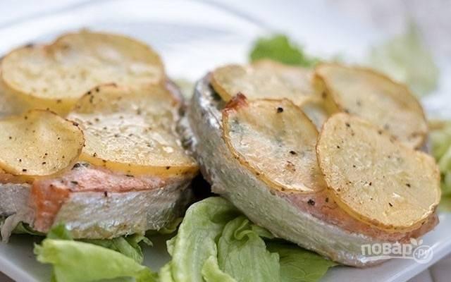 4.Запекайте рыбу при температуре 180-200 градусов в течение 25 минут, пока картофель не станет золотистого цвета, а рыба – готовой. Подайте блюдо горячим и приятного аппетита!