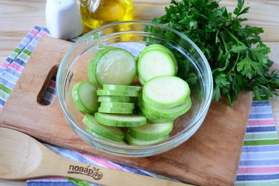 Сложите кружочки кабачка в миску, добавьте оливковое масло и аккуратно перемешайте, чтобы не разломать кружочки и масло полностью покрыло кабачки.