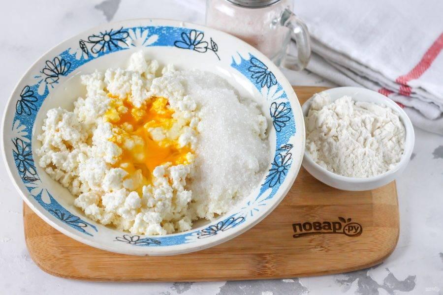 В глубокую емкость выложите творог, всыпьте сахарный песок, соль, и влейте куриное яйцо. Его можно заменить тремя перепелиными.