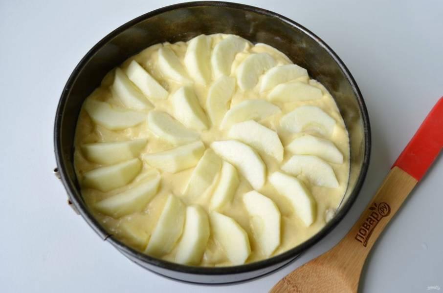 6. Включите духовку прогреваться до 200 градусов. Форму застелите пергаментом, смажьте растительным или сливочным маслом. Перелейте тесто, разровняйте. Сверху уложите красиво яблочные дольки.