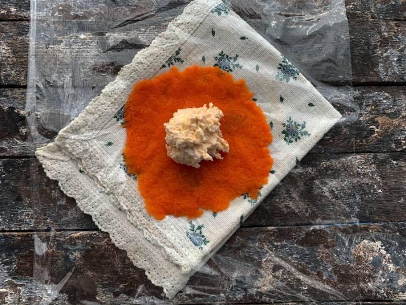 Возьмите салатную массу, сформируйте шарик в виде мандаринки и выложите на морковь.