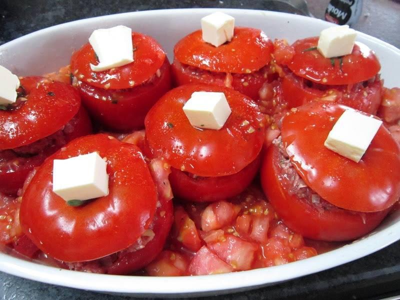 Выкладываем помидоры в форму для запекания, заливаем в нее приготовленный соус, сверху на каждый помидор кладем по кусочку сливочного масла.