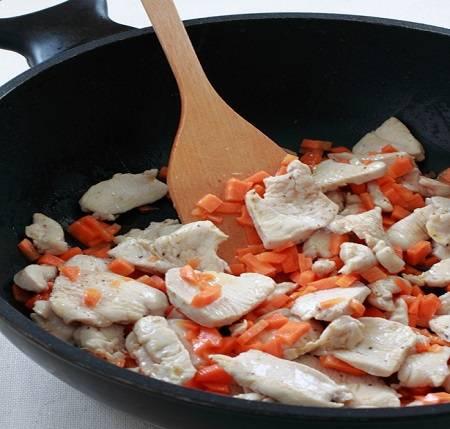 2. На сковороду налить немного растительного масла и отправить туда мясо. На среднем огне слегка обжарить, а затем добавить морковь. Периодически помешивая, жарить около 5-7 минут.
