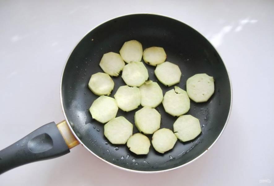 Крупный баклажан очистите, помойте и нарежьте кружками толщиной 5-7 мм. Выложите в горячую сковороду с рафинированным подсолнечным маслом.