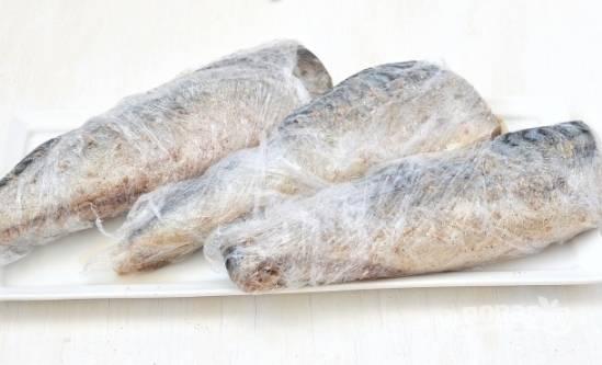 Плотно заворачиваем рыбу в пищевую пленку и отправляем в холодильник на пару часов, а затем в морозильную камеру минимум на 24 часа.