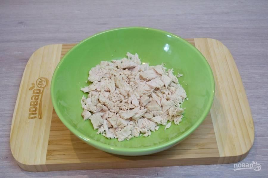 1. Для приготовления салата нам необходимо отварить куриное филе. Остывшее мясо нарезаем на небольшие кусочки. Размер выбирайте на свой вкус. Измельченное мясо поместите в миску.