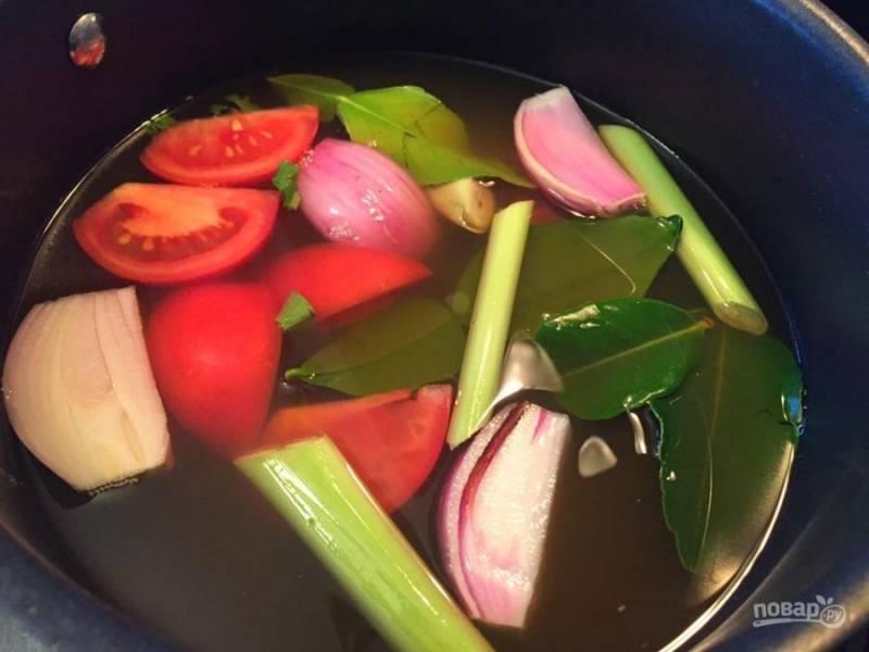 В кастрюльке на среднем огне доведите до кипения бульон с лимонной травой, листьями лайма, шалотом, имбирем, томатом и рыбным соусом.