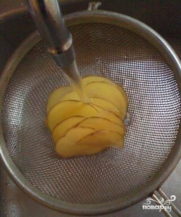 Промываем нарезанный картофель под струей воды.