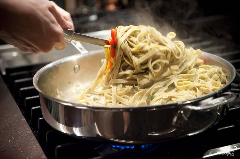 Фетучини добавляем в сковороду к курице и хорошо все перемешиваем, вливаем немного воды, чтобы избежать сухости.
