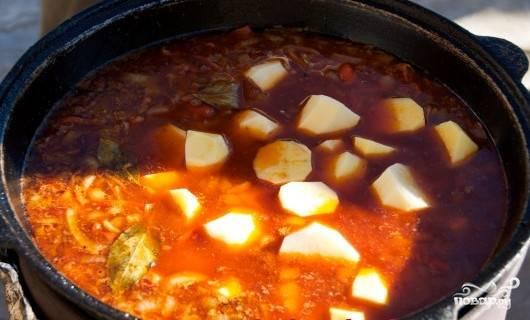 Добавить в казан почищенный и нарезанный пополам картофель.