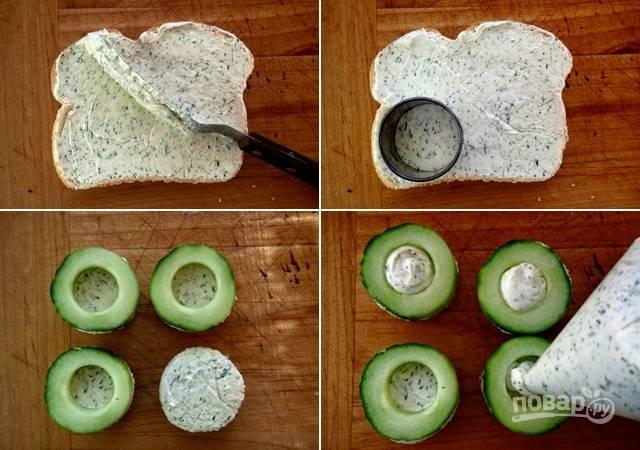 4. Ломтик хлеба немного смажьте полученной сырной пастой. Вырежьте выемкой кружочек. Сверху выложите огурчик и наполните его пастой, используя кондитерский мешок или полиэтиленовый пакет.