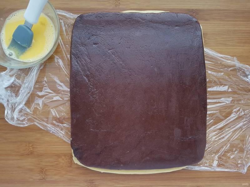 На белый пласт положите шоколадный, слегка прижмите.