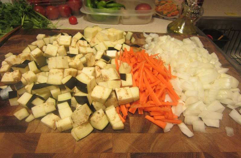 2. Луковицы, морковь и баклажан очистить и нарезать. Отправить в горячее масло, в котором обжаривалось мясо. Периодически помешивая, жарить около 5-7 минут на среднем огне.