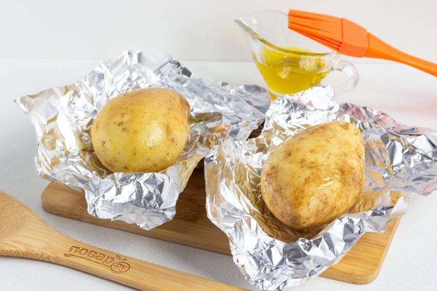 Фольгу нарежьте такими кусками, чтобы можно было обернуть каждый клубень по отдельности. Выложите картофель в фольгу и смажьте кулинарной кистью оливковым маслом.