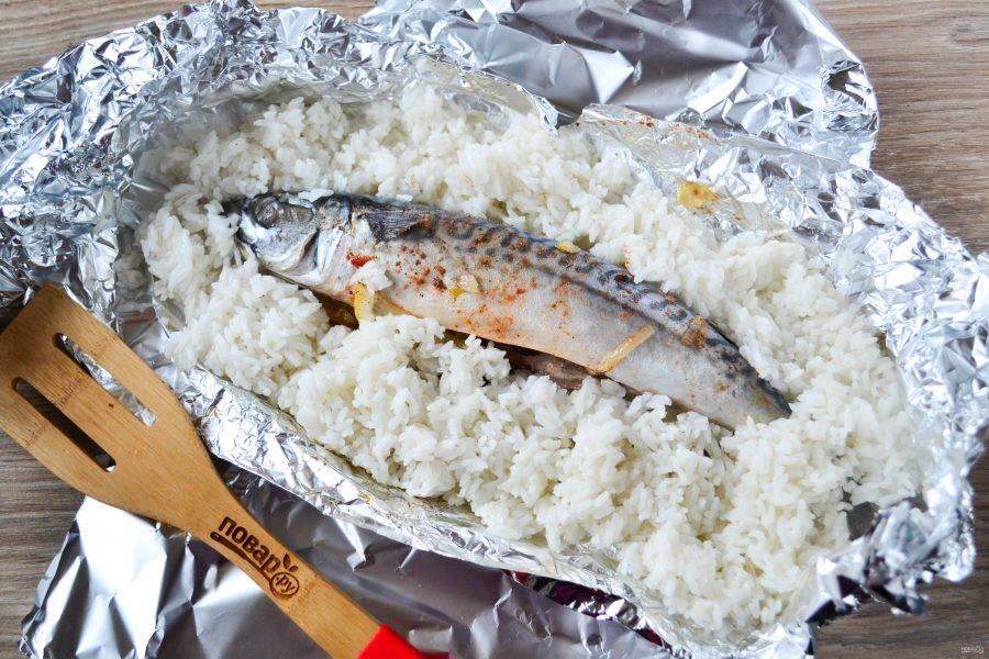 Затем извлеките скумбрию из духовки, разверните фольгу, рыбу обложите готовым рисом, заверните снова фольгу и отправьте в духовку еще на 15 минут.