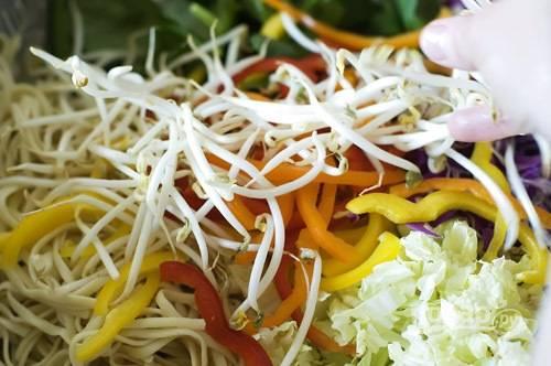 4. Смешайте нашинкованную пекинскую, фиолетовую капусту, болгарский перец, огурец, шпинат, лук и кешью.