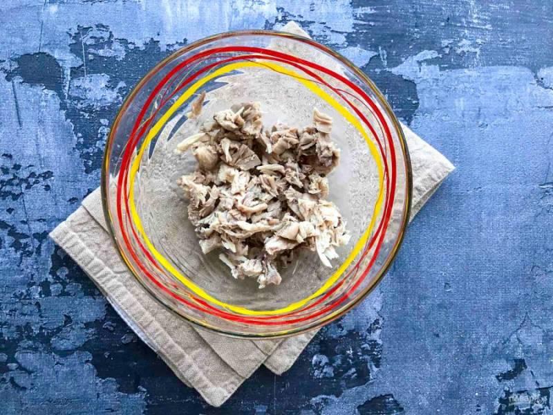 Отварное куриное филе нарежьте маленькими кусочками и выложите в тарелку.