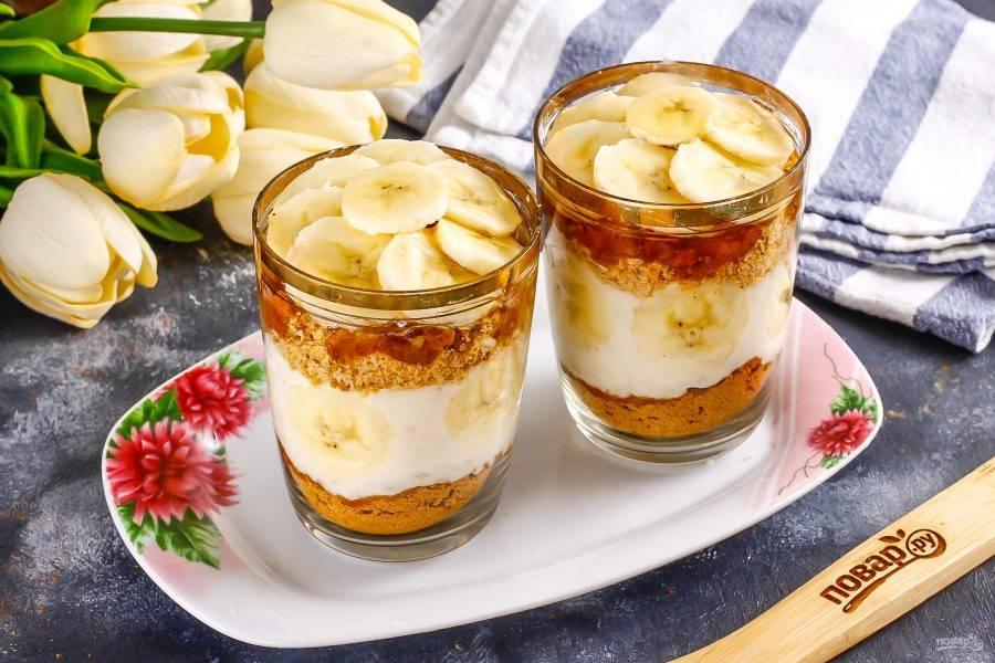 Присыпьте оставшейся песочной крошкой. Выложите сверху оставшиеся ломтики бананов и полейте их оставшимся медом. Поместите пирожные в холодильник для пропитки примерно на 30 минут, можно оставить и на ночь.