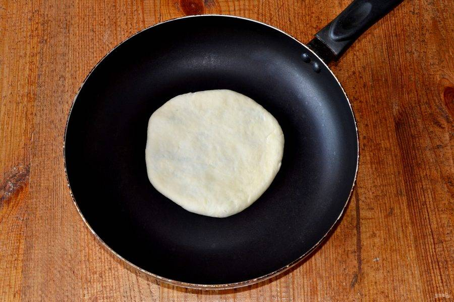 Переверните лепешку швом вниз, аккуратно раскатайте скалкой и выложите на разогретую сухую сковороду.