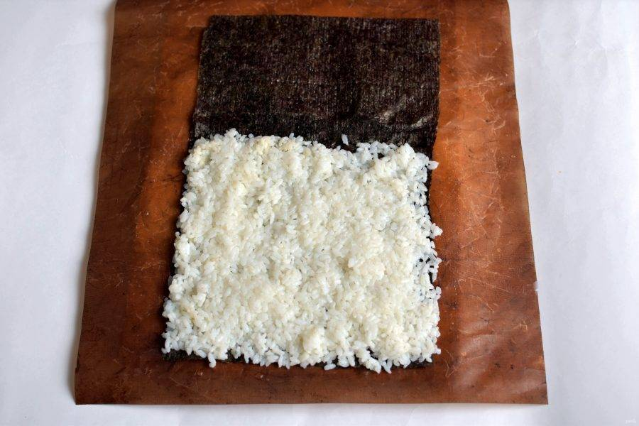 Разложите лист нори на коврике. Смочите один край водой и приклейте к нему половинку еще одного листа нори – у суширитто довольно большой размер. Влажными руками разложите слой риса, оставляя приклеенную половинку чистой.