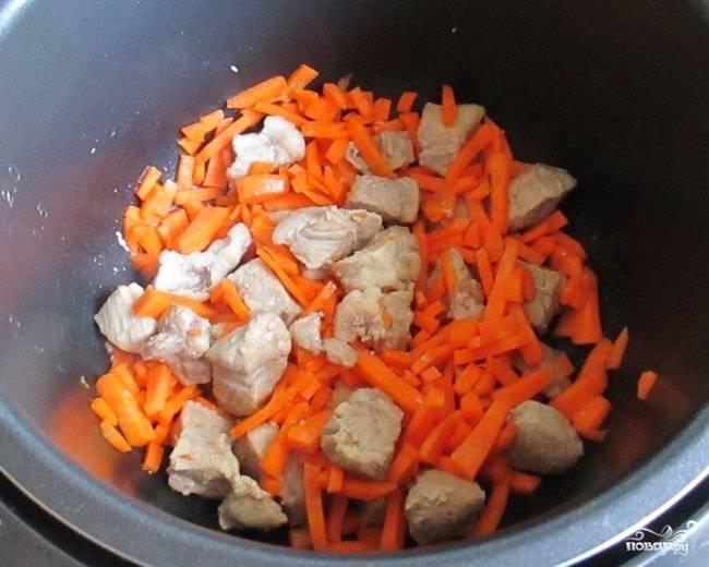 3. Помытую и очищенную морковь нарежьте крупной соломкой. Морковку выложите к мясу в мультиварочную чашу. Продолжайте готовить в режиме «Выпечки» последующие 5 минут.