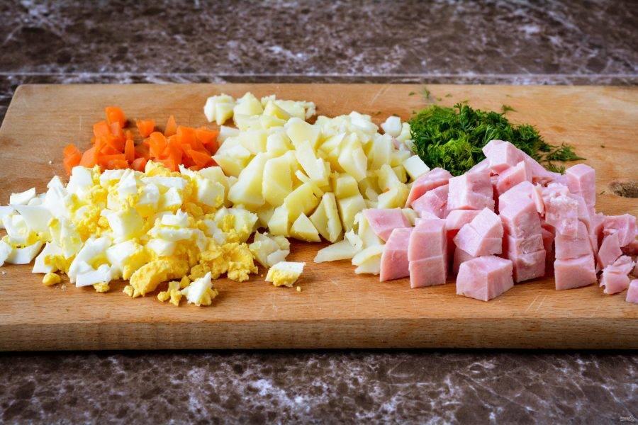 Заранее сварите картофель и морковку до мягкости, варятся корнеплоды около 20 минут. Также сварите вкрутую куриные яйца. Сваренные компоненты остудите и нарежьте кубиками - картофель, морковку и яйца. Также нарежьте кубиками и ветчину. Мелко нарежьте свежий укроп.
