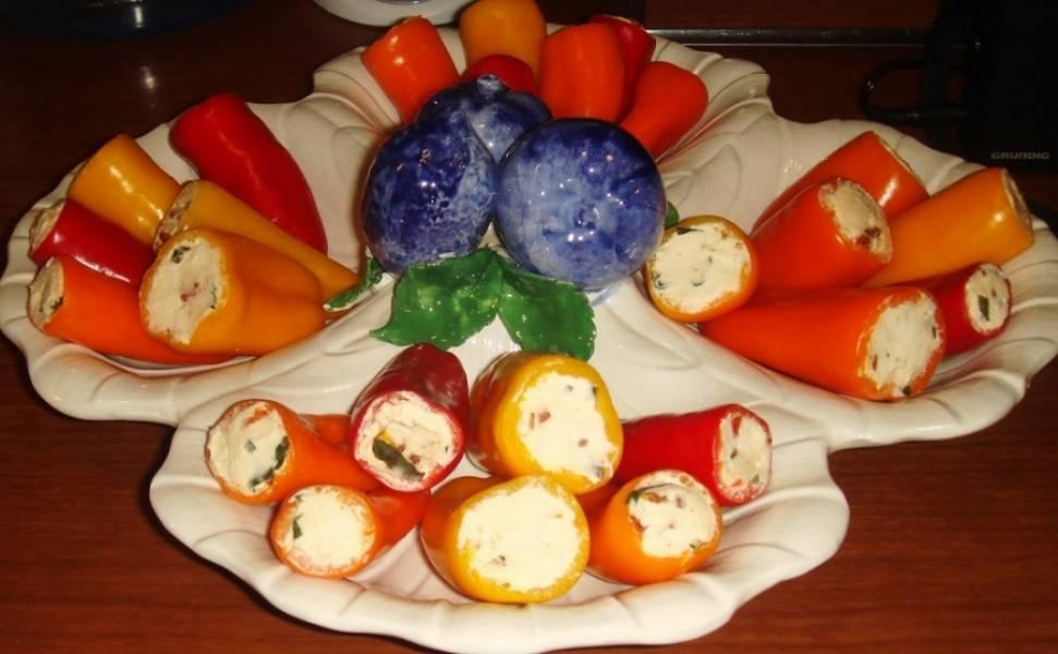 3. Перец с чесночной начинкой отправьте в холодильник, чтобы начинка застыла. Перед подачей перчики можно нарезать кружочками острым ножом, особенно, если у вас перцы - большие. К такой закуске обычно подают тосты, жареный черный хлеб или рисовые сухарики. Приятного аппетита!