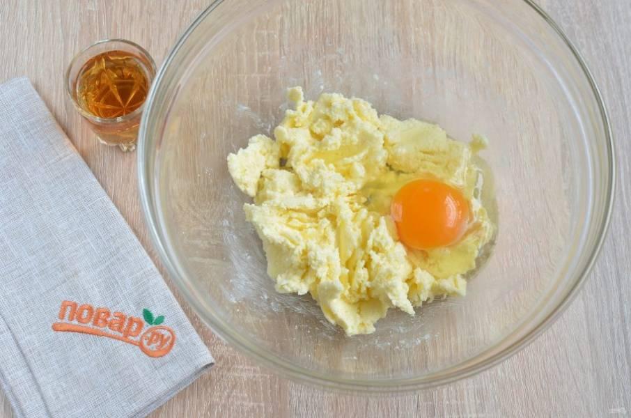 2. Масло соедините с сахаром, разотрите хорошо миксером или вилочкой. Добавьте яйцо, перемешайте. Влейте коньяк, снова перемешайте хорошо.
