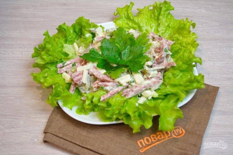5. На листья салата выложите заправленный майонезом салата. В центре сделайте углубление и заполните его петрушкой.