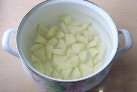 1. Картошку помойте и очистите от кожуры, нарежьте её кубиками. В кастрюлю подходящего объема налейте холодную воду, поставьте на огонь, всыпьте нарезанный картофель.