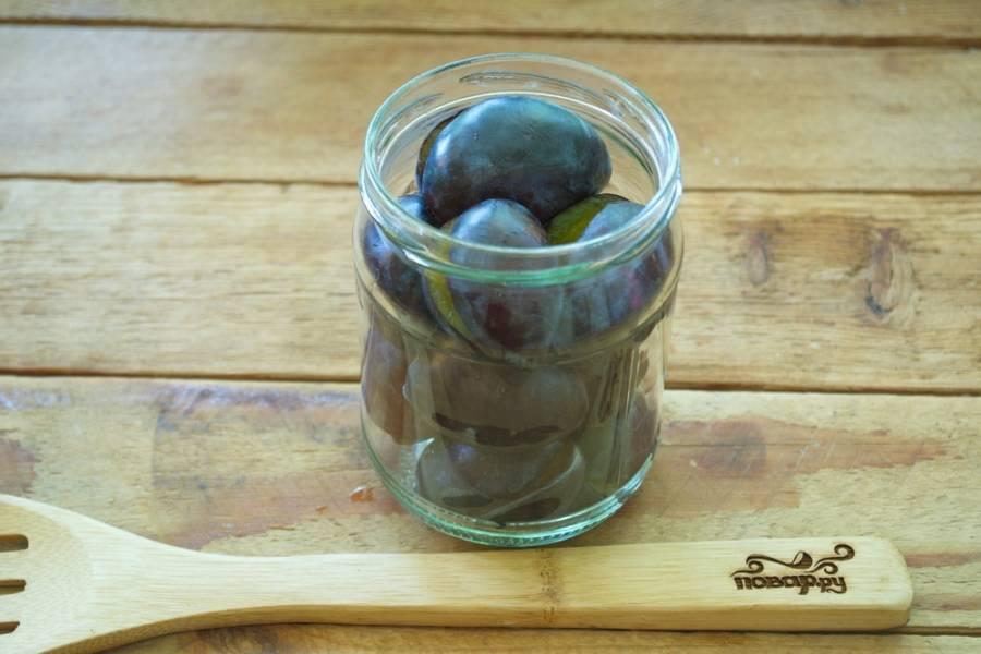 В каждую стерильную  баночку добавьте по паре бутончиков гвоздики, пару горошин душистого перца, затем заполните баночки сливами.