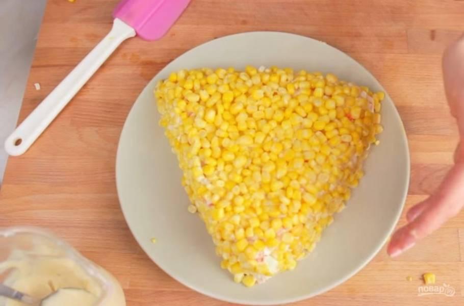 2. Далее с помощью лопатки выложите и сформируйте из салата треугольник. Посыпьте его кукурузой. При необходимости вытрите тарелку бумажным полотенцем.