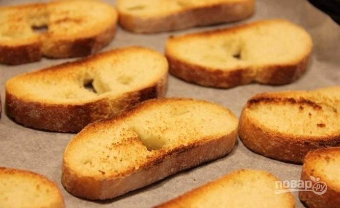 Батон нарежьте ломтиками в 1,5 см толщиной. Обжарьте их на сухой сковороде с двух сторон до  лёгкой румяности. Делайте это на медленном огне.