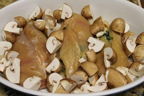 7. Также поступить и с остальными кусочками курицы. Грибы вымыть, обсушить и нарезать на 4-6 частей (в зависимости от размера). Выложить в форму.