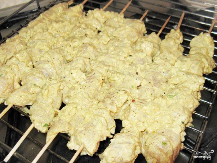 4. Разогреть духовку до 180 градусов. Нанизать мясо на шпажки и выложить на решетку. Внизу установить противень.