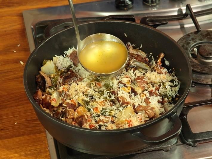 Долейте бульон и тушите до готовности риса.