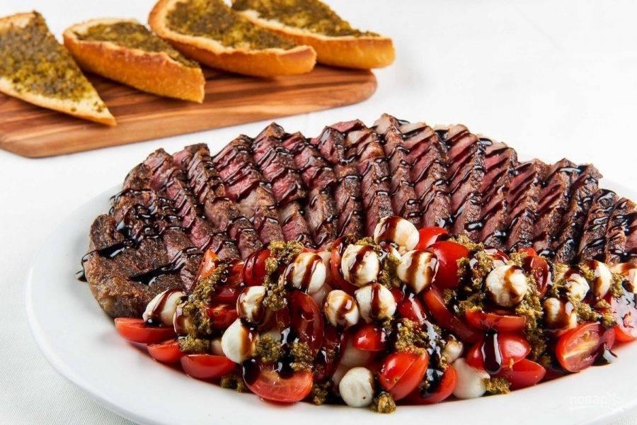 4. Когда стейк немного остынет, нарежьте его слайсами. Рядом выложите помидоры и сыр. Полейте ингредиенты уксусом и соусом. Также на соседней тарелке подайте багет. Приятного аппетита!